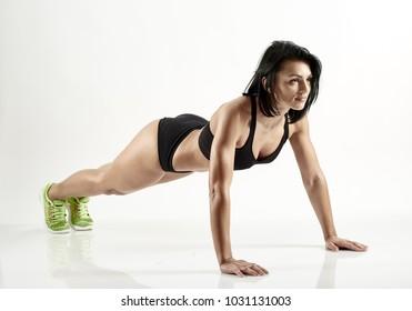 Young hispanic female fitness model doing pushups on white background
