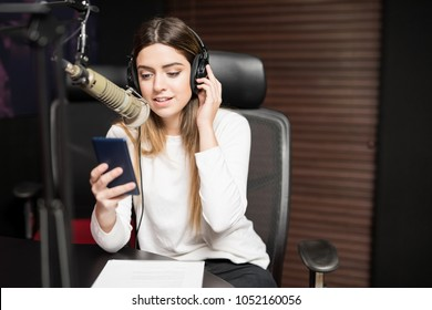 Young hispanic female host communicating on microphone in radio studio with headphones and mobile phone