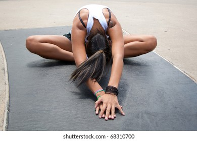 young hispanic female stretching outside before a run