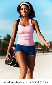 Young Hispanic Fitness Woman Goofing Off on Beach