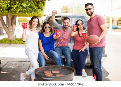Young Hispanic friends celebrating the victory of their football team while drinking and having fun at a barbecue