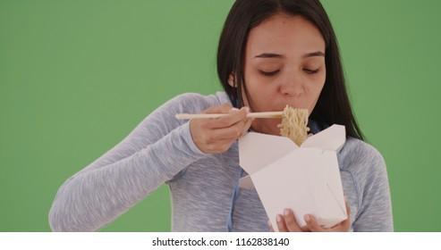 Young hispanic girl eating chinese food on green screen
