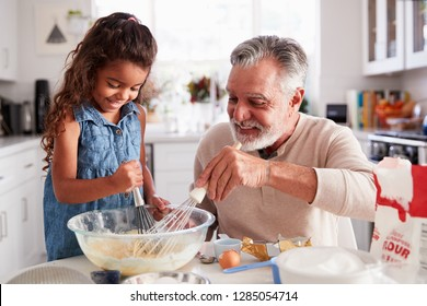 Young Hispanic girl and her grandad whisking cake mixture together at the kitchen table, close up