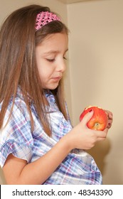 young Hispanic girl  looking down at her apple