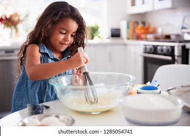 Young Hispanic girl making a cake in the kitchen on her own, close up