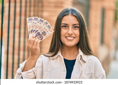 Young hispanic girl smiling happy holding mexican 500 pesos banknotes at the city.