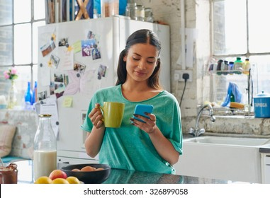 Young hispanic girl smiling using blue mobile phone holding coffee painted finger nails at home in kitchen wearing pajamas