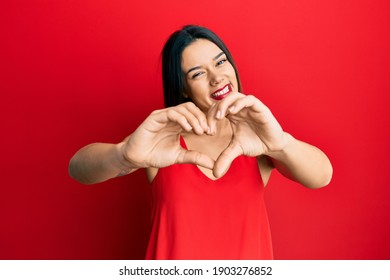 Young hispanic girl wearing casual style with sleeveless shirt smiling in love doing heart symbol shape with hands. romantic concept.