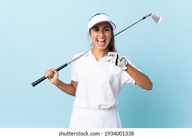 Young hispanic golfer woman over isolated blue wall surprised and pointing front
