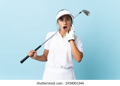 Young hispanic golfer woman over isolated blue wall with surprise and shocked facial expression