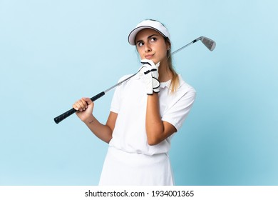 Young hispanic golfer woman over isolated blue wall and looking up