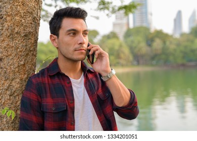 Young Hispanic hipster man talking on the phone at the park