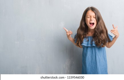 Young hispanic kid over grunge grey wall shouting with crazy expression doing rock symbol with hands up. Music star. Heavy concept.