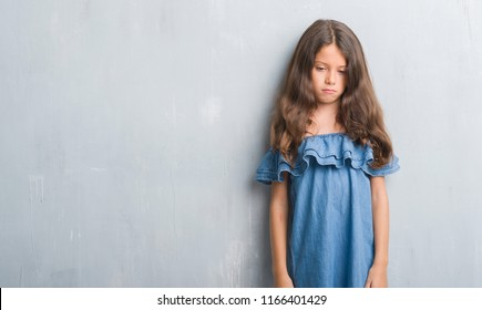 Young hispanic kid over grunge grey wall depressed and worry for distress, crying angry and afraid. Sad expression.