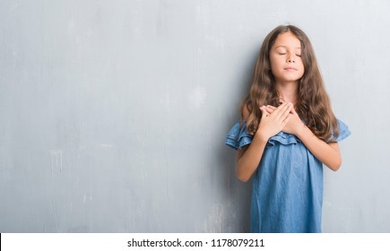 Young hispanic kid over grunge grey wall smiling with hands on chest with closed eyes and grateful gesture on face. Health concept.