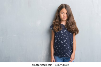 Young hispanic kid over grunge grey wall skeptic and nervous, frowning upset because of problem. Negative person.