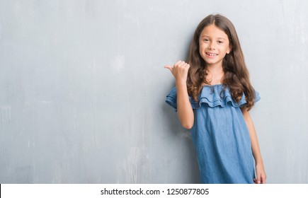 Young hispanic kid over grunge grey wall amazed and surprised looking up and pointing with fingers and raised arms.