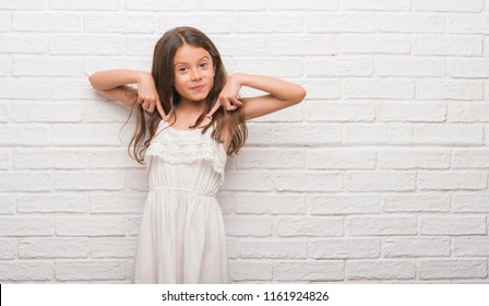 Young hispanic kid over white brick wall looking confident with smile on face, pointing oneself with fingers proud and happy.