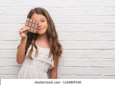 Young hispanic kid over white brick wall eating chocolate bar with a happy face standing and smiling with a confident smile showing teeth