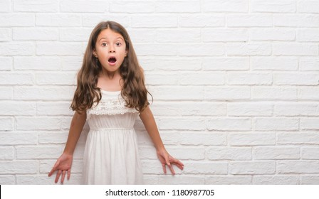 Young hispanic kid over white brick wall afraid and shocked with surprise expression, fear and excited face.