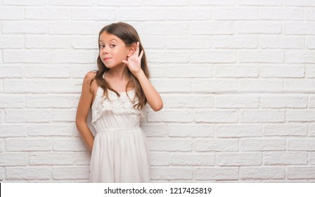 Young hispanic kid over white brick wall smiling with hand over ear listening an hearing to rumor or gossip. Deafness concept.