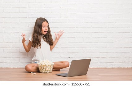 Young hispanic kid sitting on the floor eating popcorn and watching a movie very happy and excited, winner expression celebrating victory screaming with big smile and raised hands