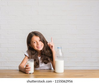 Young hispanic kid sitting on the table drinking a glass of milk surprised with an idea or question pointing finger with happy face, number one