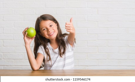 Young hispanic kid sitting on the table eating fresh green apple happy with big smile doing ok sign, thumb up with fingers, excellent sign