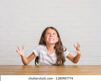 Young hispanic kid sitting on the table at home crazy and mad shouting and yelling with aggressive expression and arms raised. Frustration concept.