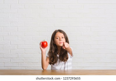 Young hispanic kid sitting on the table eating fresh tomato pointing with finger to the camera and to you, hand sign, positive and confident gesture from the front