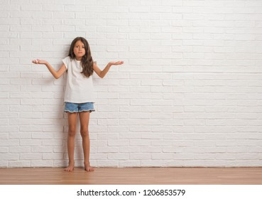 Young hispanic kid stading over white brick wall clueless and confused expression with arms and hands raised. Doubt concept.