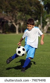 Young Hispanic or Latino boy playing soccer in a field with blue shorts with copy space above