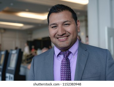 Young hispanic or latino businessman walking in a clean grey purple business attire out of a building from a meeting to greet the camera with a smile.
