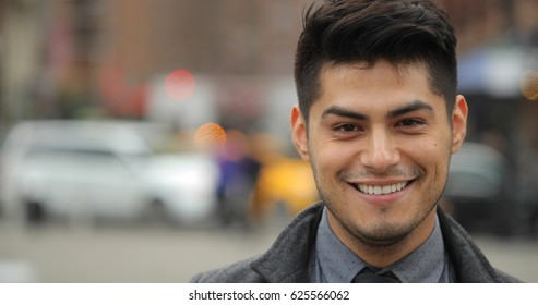 Young Hispanic Latino man in city face portrait smile happy