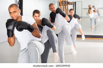 Young hispanic male wearing boxing gloves in group workout time in self-defense in gym