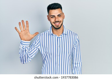 Young hispanic man with beard wearing casual striped shirt showing and pointing up with fingers number five while smiling confident and happy.