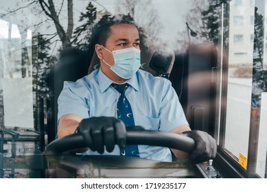 young hispanic man bus driver  in a protective mask and black gloves. prevent the spread of coronavirus. young hispanic bus driver wearing a protective mask and looks at road. quarantine. covid 19.