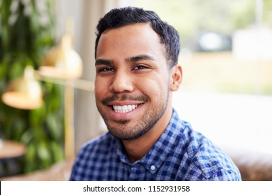 Young Hispanic man in coffee shop smiling to camera