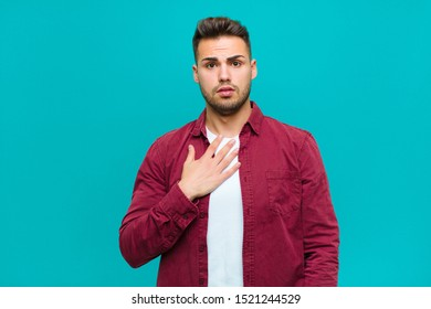 young hispanic man feeling shocked, astonished and surprised, with hand on chest and open mouth, saying who, me? against blue background