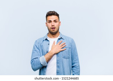 young hispanic man feeling shocked, astonished and surprised, with hand on chest and open mouth, saying who, me? against blue wall