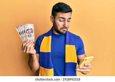 Young hispanic man football supporter using smartphone holding mexican pesos banknotes depressed and worry for distress, crying angry and afraid. sad expression.