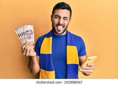 Young hispanic man football supporter using smartphone holding mexican pesos banknotes sticking tongue out happy with funny expression.
