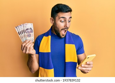 Young hispanic man football supporter using smartphone holding mexican pesos banknotes celebrating crazy and amazed for success with open eyes screaming excited.