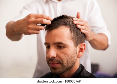 Young Hispanic man getting a haircut at a barber shop