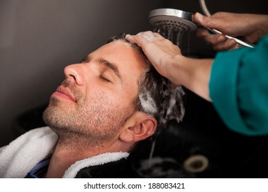 Young Hispanic man getting pampered with a hair wash and head massage in a hair salon