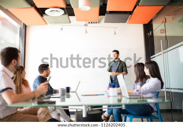 Young hispanic man giving a sales pitch to his business team in a conference room