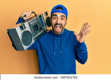 Young hispanic man holding boombox, listening to music celebrating victory with happy smile and winner expression with raised hands  - Shutterstock ID 1897651702