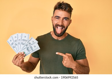 Young hispanic man holding dollars sticking tongue out happy with funny expression.