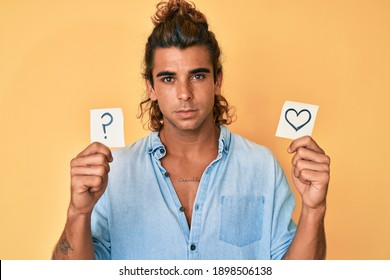 Young hispanic man holding heart and question mark reminder relaxed with serious expression on face. simple and natural looking at the camera.