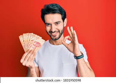 Young hispanic man holding mexican pesos doing ok sign with fingers, smiling friendly gesturing excellent symbol